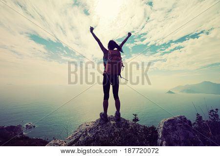 successful woman backpacker hiking on mountain peak