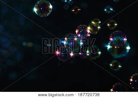 Rainbow soap bubbles with blurred on a dark backgrounds
