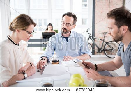 Serious manager is helping female colleague with project. Male coworker holding tablet. They are sitting around common desk