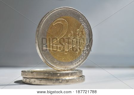 Macro detail of a silver and golden coin in value of two Euros (EUR, Euro) on white and silver background as a symbol of European currency