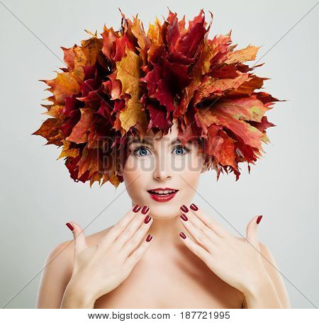 Autumn Concept. Beautiful Woman with Wreath of Red Maple Leaves Autumn Fashion Makeup and Manicure