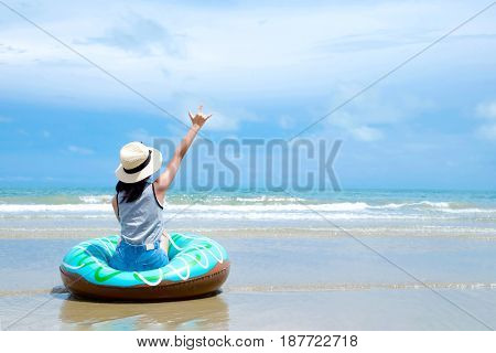 Woman sitting on swim ring with love hand sign gesture over blue sky at summer beach background travel holiday vacation concept