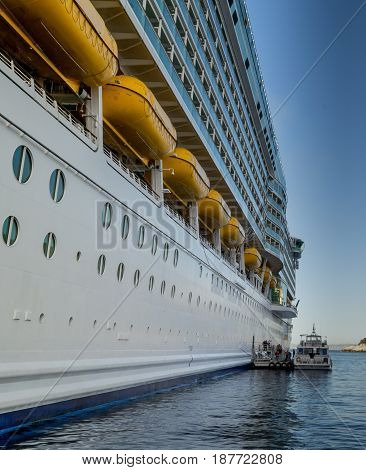 Port side of a giant cruise chip anchored in the Mediterranean Sea and tender boat prepares to pick up passengers