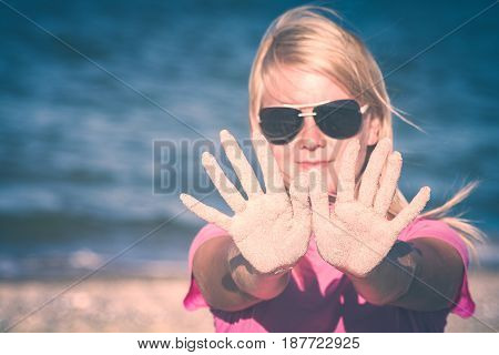 Girl in sunglasses show hands covered with sand on a blue sea background. Instagram stylisation.