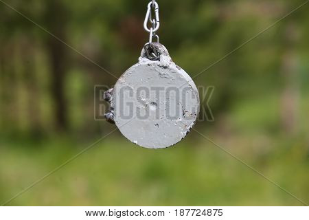 Target for training shooting. Metal on the chain.