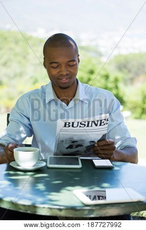 Young businessman reading business newspaper at restaurant