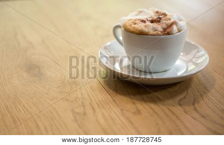 Close-up of coffee cup with creamy froth on table at cafe