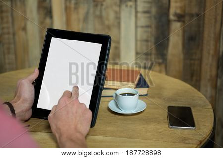 Cropped image of man using digital tablet with blank screen in coffee shop