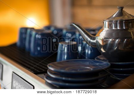 Close-up of kettle with cups and saucers on counter in coffee shop