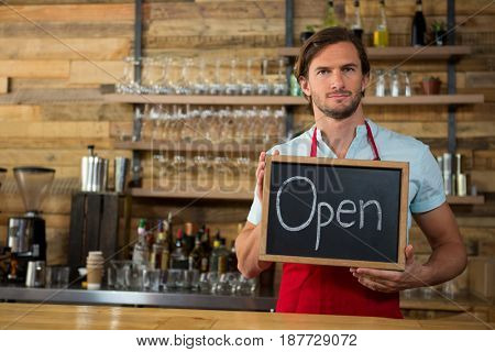 Portrait of male barista holding open signboard in coffee shop
