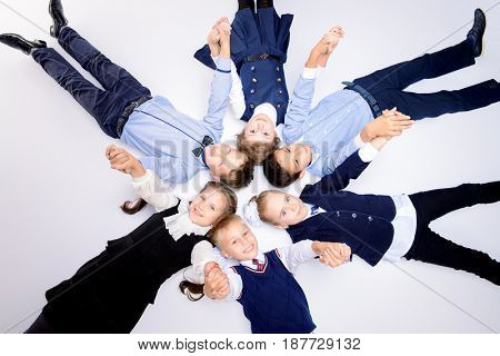Group of happy school children posing together at studio. School uniform. Educational concept. Isolated over white.