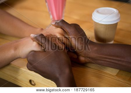 Close-up of multi ethnic couple holding hands in coffee shop