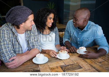 Multi ethnic friends talking while having coffee at table in coffee shop