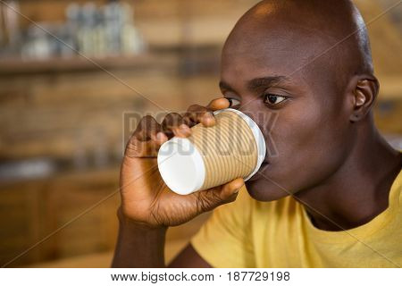 Close-up of young man drinking coffee from disposable cup in cafe