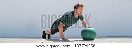 Fitness man banner crop. Athlete strength training pushup chest and shoulder muscles doing alternating single arm medicine ball push-ups floor exercises at outdoor gym.