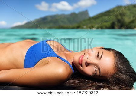 Bikini woman tanning on overwater bungalow terrace enjoying luxury travel holidays. Asian beauty smiling in Tahiti, French Polynesia.
