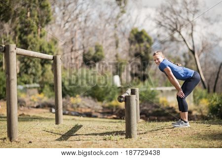 Fit woman standing with her hands on knee at boot camp