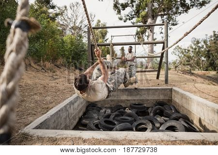 Young military soldiers practicing rope climbing during obstacle course at boot camp