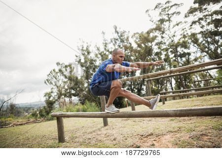 Fit man balancing on hurdles during obstacle course training at boot camp