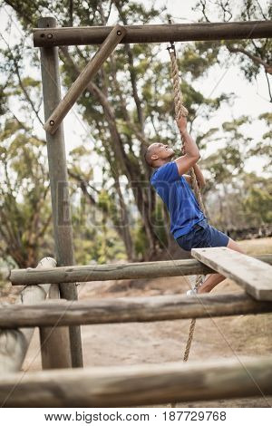 Fit man climbing a rope during obstacle course in boot camp