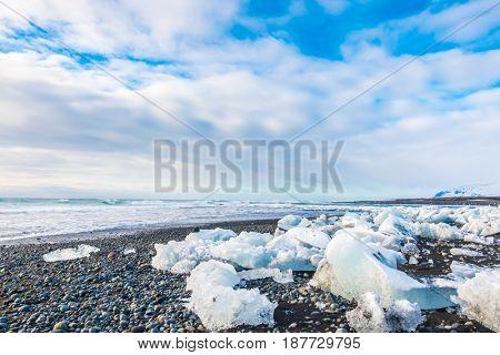 Ice cube breaking on black rock beach , Iceland winter season landscape