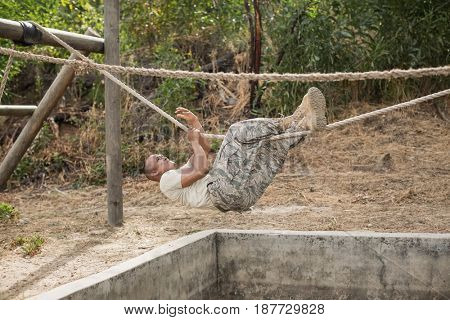 Military soldier climbing rope during obstacle course training at boot camp