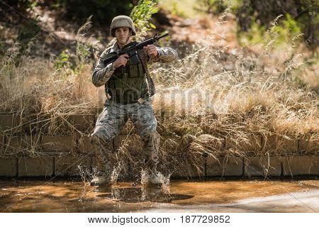 Military soldier with rifle jumping in water in boot camp