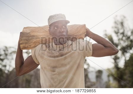 Military soldier carrying a tree log during obstacle course in boot camp