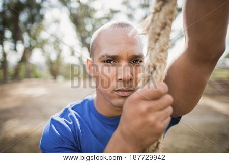 Portrait of fit man climbing rope during obstacle course in boot camp