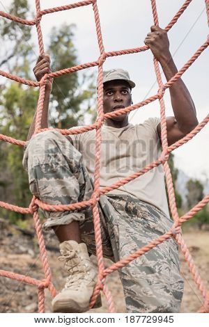 Military soldier climbing a net during obstacle course in boot camp