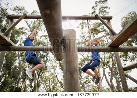 Fit man and woman climbing rope during obstacle course in boot camp