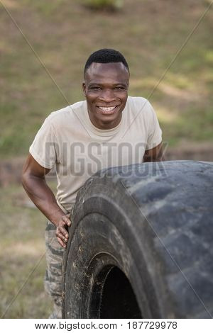 Portrait of happy military soldiers exercising with tyre in boot camp