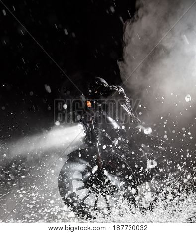Detail of high power motorcycle chopper with man rider at night. Fog with backlights on background. Water splash on foreground