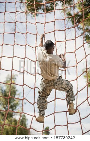 Military soldier climbing net during obstacle course in boot camp