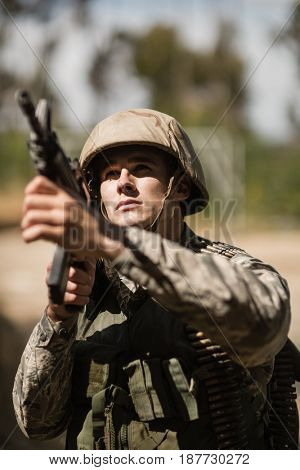 Military soldier aiming with a rifle in boot camp