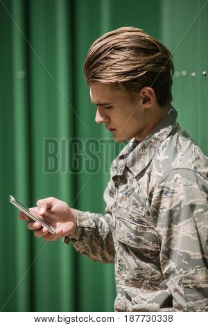Military soldier using mobile phone in boot camp