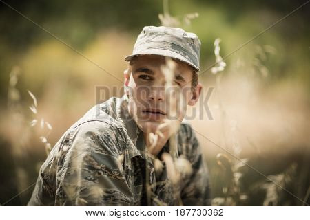 Thoughtful military soldier relaxing in grass in boot camp