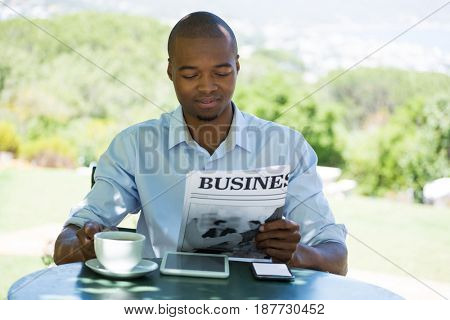 Young man reading business newspaper at restaurant