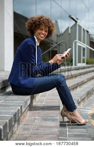 Businesswoman using mobile phone in the office premises