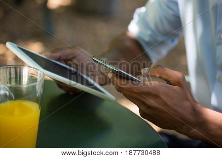 Cropped image of man holding mobile phone and digital tablet at restaurant