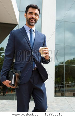 Portrait of businessman holding disposable cup and diary near office building