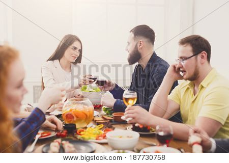Happy couple celebrate, have dinner with friends in restaurant or at home party. People have meals together, friendly conversation