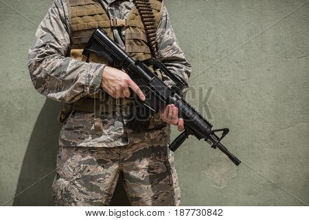 Mid section of military soldier standing with a rifle against concrete wall in boot camp