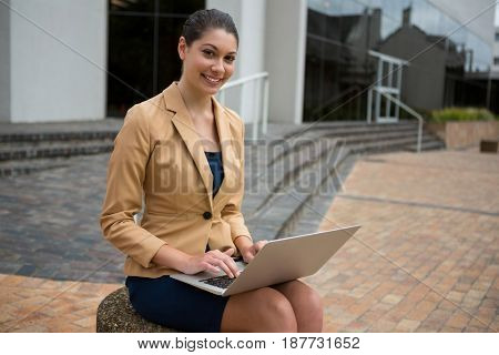 Portrait of smiling businesswoman using laptop in the office premises