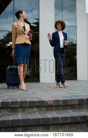 Businesswoman walking with luggage bag near office building