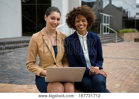 Two businesswomen using laptop in the office premises