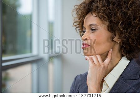 Thoughtful businesswoman looking through window in the office