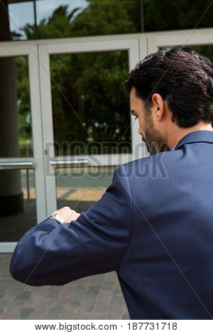 Businessman checking time while walking in office building
