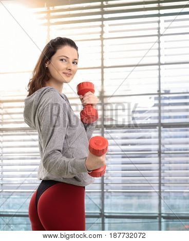 Healthy teenage girl exercising with hand barbell, smiling.