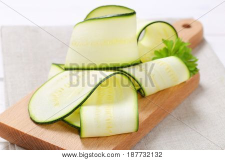 pile of raw zucchini strips on wooden cutting board - close up